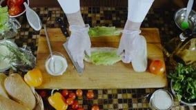 Kock Puts Salad Leaf på en smörgås stock video