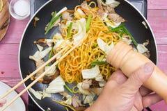 Kock satt peppar för att laga mat den Yakisoba nudeln Arkivfoto