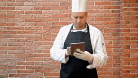 Kock som använder hans digitala minnestavla i köket Arkivbild