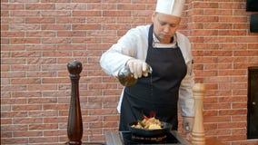 Kock som avslutar maträtten som sätter olja till en platta Fotografering för Bildbyråer