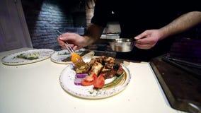 Kock som bevattnar sås och kryddar stycken av den färdiga kebaben lager videofilmer
