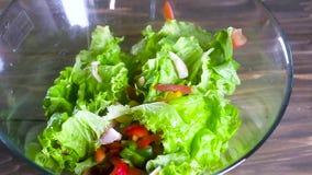Kock som bevattnar sallad med olivolja en tunn ström av olja häller överst av en ny sallad av naturliga grönsaker i en stor expon lager videofilmer