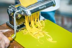 Kock som förbereder hemlagad tagliatelle med maskinen, selektiv fokus arkivbilder