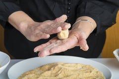 Kock som förbereder kroketter i köket fotografering för bildbyråer