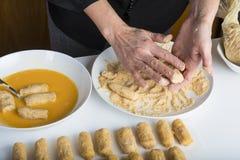 Kock som förbereder kroketter i köket arkivbild