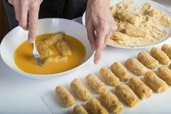 Kock som förbereder kroketter i köket royaltyfri bild