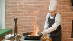 Kock som förbereder skaldjur i panna med alkohol i stor flamma Arkivbild