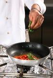 kock som förbereder tomaten arkivfoto