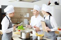 Kock som förklarar matlagningtekniker royaltyfria bilder