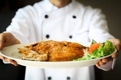 Kock som framlägger proudly den stekte fisken för havsbas på den vita plattan royaltyfri bild