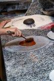 Kock som gör en pizza med ost i en restaurang Arkivfoton