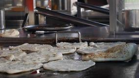 Kock som gör mycket traditionell indisk mat som kallas 'Roti Canai ', 4K lager videofilmer