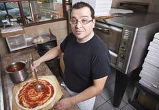 kock som gör pizzasåsfördelning royaltyfri bild