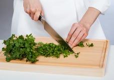 Kock som hugger av ny persilja arkivbild