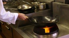 Kock som kastar grönsaker över en stor flamma stock video