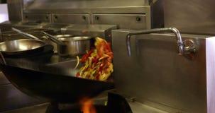 Kock som kastar grönsaker i en woka över en stor flamma stock video