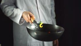 Kock som kastar grönsakuppståndelsesmåfisk i en woka lager videofilmer