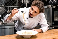 kock som kontrollerar pasta med gaffeln arkivbilder