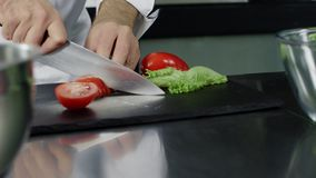 Kock som lagar mat ny sallad på kök Closeupkockhänder som klipper tomaten lager videofilmer