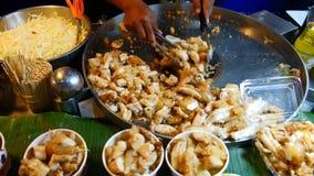 Kock som lagar mat stekte under omrörning till salu tioarmad bläckfiskägg, Thailand stock video