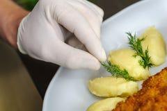 Kock som ordnar en matställe Arkivfoto