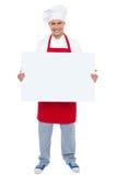 Kock som rymmer den blanka vita affischtavlan Arkivbilder