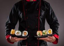 Kock som rymmer plattor med sushistycken royaltyfria bilder