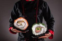Kock som rymmer plattor med sushistycken royaltyfria foton