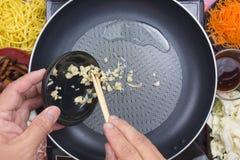 Kock som sätter finhackad vitlök för att laga mat Yakisoba Arkivfoto