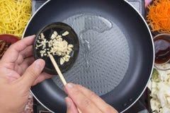 Kock som sätter finhackad vitlök för att laga mat Yakisoba Arkivbild