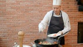 Kock som sätter skedar med kryddor till pannan, prepearing skaldjur Royaltyfri Fotografi