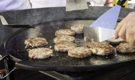 Kock som steker hamburgare royaltyfri fotografi