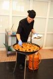 Kock som tillfogar det sista handlaget till paella, skalen royaltyfri foto