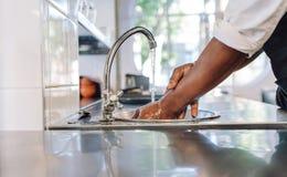 Kock som tvättar hans händer i kommersiellt kök royaltyfri bild