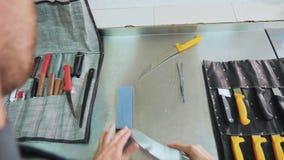 Kock som vässar en kniv, närbild lager videofilmer
