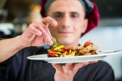 Kock som visar stolt mat eller maträtten som han lagade mat Royaltyfri Fotografi