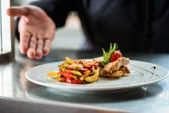 Kock som visar stolt mat eller maträtten som han lagade mat Arkivfoton