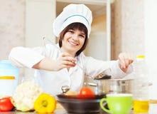 tillfogar salt eller kryddor in i soppa Arkivfoton
