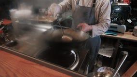 Kock Tossing Fried Vegetables With Meat In en stekpanna, kommersiell kökmatlagning arkivfilmer