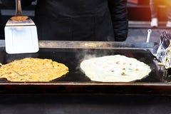 Kockar är stekte omelett blandade med grönsaker och champinjoner, gatamat royaltyfri bild