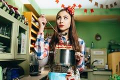 Kockar för ung kvinna i köket Royaltyfri Fotografi