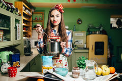 Kockar för ung kvinna i köket Arkivbilder