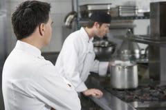 Kockar som arbetar i kök royaltyfria foton