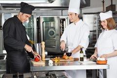 Kockar som arbetar i kommersiellt kök Arkivbild