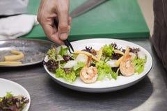 Kockar som förbereder en sallad av skaldjur royaltyfri foto