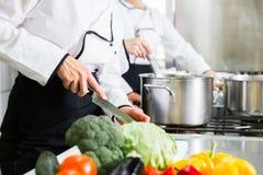 Kockar som förbereder mål i kommersiellt kök royaltyfria foton