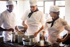 Kockar som förbereder mat på ugnen royaltyfri fotografi