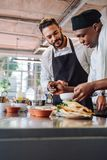 Kockar som lagar mat den nya matmaträtten i kök arkivbilder