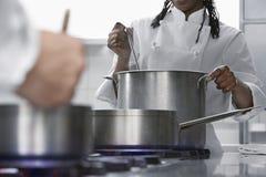 Kockar som lagar mat i kök arkivfoto