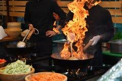 Kockar som lagar mat med flamman i en stekpanna royaltyfri bild